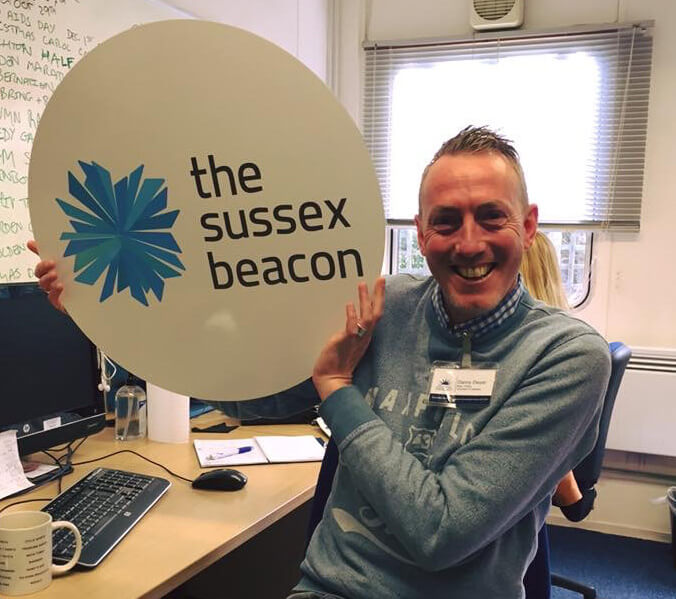 "by: Kirsty Charlton 10/05/2016 We at Reade Signs are well known for our charitable efforts, donations and contributions, and when 'The Sussex Beacon' – a Brighton-based charity that provides care and support for men, women and families living with HIV - underwent a rebrand, we were happy to support them by donating signage incorporating their new logo. Simon Dowe, CEO of the charity is delighted with the signage, commenting ""many people have already commented on how fabulous the signs look, both outside and in our reception area…it is only though the generosity of people like you that we are able to continue our work"". We are very pleased to have provided the Sussex Beacon with their rebranding signage as part of our #reade35 challenge, celebrating 35 years of successful trading by supporting 35 community based initiatives over the past year. The Sussex Beacon Volunteer Fundraiser Danny Dwyer was thrilled with the new donated signage The Sussex Beacon Volunteer Fundraiser Danny Dwyer was thrilled with the new donated signage Back"
